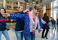 ORLANDO, FL - FEBRUARY 28: Ashlyn Harris #18 of the United States helps put a coat on during a SheBelieves press conference at City Hall on February 28, 2020 in Orlando, Florida.