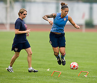 USWNT forward Natasha Kai jumps across a set of hurdles as strength and fitness coach Helena Andersson watches during practice at Beijing Normal University in preparation for the Olympic gold medal game at Workers' Stadium in Beijing, China.