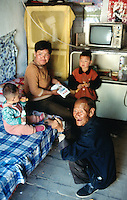 China. Province of Shaanxi. Village Shifeng. Li Hupeng is the boy's name. He was kidnapped on may 12 2002, sold to a family in the village of Xiaotan in Henan province. The police found him and brought him back to his family on march 4 2004. Li Hupeng stays near his mother and his little sister, seated on a bed, while his old grand father kneels down in the traditionnal chinese way. © 2004 Didier Ruef