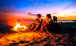 A couple cooks hotdogs on the beach at sunset at Shell Point Beach in the north Florida panhandle.