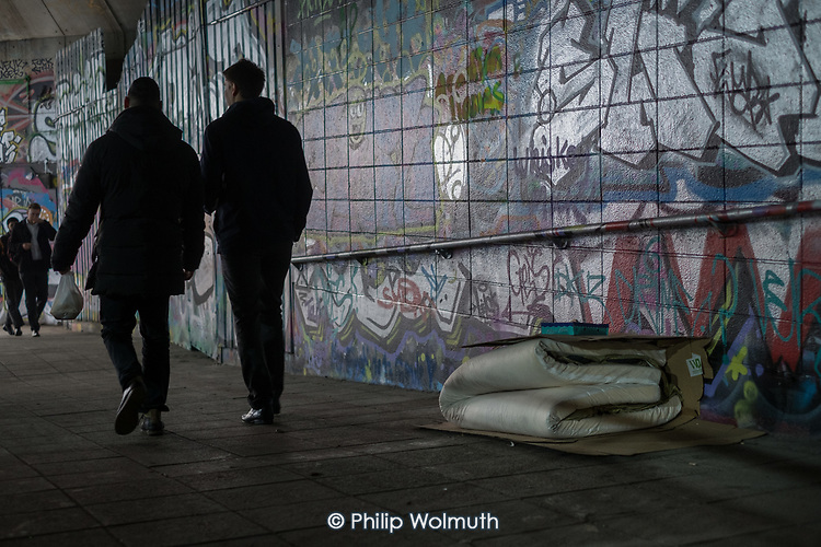Pedestrians pass a mattress and cardboard belonging to a rough sleeper, Waterloo, London.
