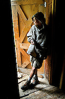 Photo story of Philmont Scout Ranch in Cimarron, New Mexico, taken during a Boy Scout Troop backpack trip in the summer of 2013. Photo is part of a comprehensive picture package which shows in-depth photography of a BSA Ventures crew on a trek. In this photo BSA Ventures crew steps inside a doorway to get out of the heavy rains falling at Black Mountain Camp in the backcountry of Philmont Scout Ranch.   <br /> <br /> The  Photo by travel photograph: PatrickschneiderPhoto.com