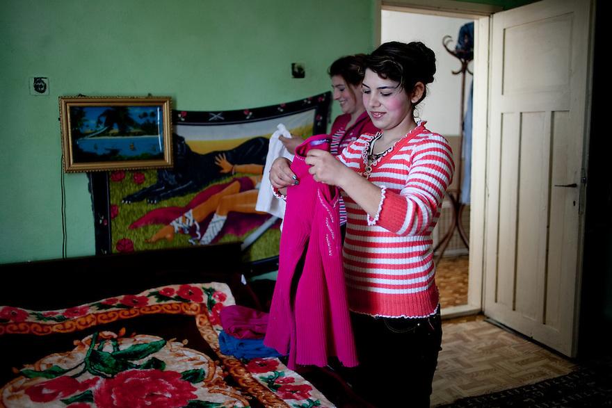 Kalaidzhii Women --For a Story by Matthew Brunwasser -Female Factor series- on nomadic Tinkerers of Thrace .[Caption : ] Oryahovitsa, Bulgaria, Kalaidzhii (245 km east of Sofia) March 13, 2010. Anka Vasileva, 14, and her cousin Galya Kostova, 17, folding laundry. Anka says she does not plan to marry young, according to Kalaidzhii tradition, but instead hopes to study medicine. [Credit:] //// JODI HILTON for the International Herald Tribune