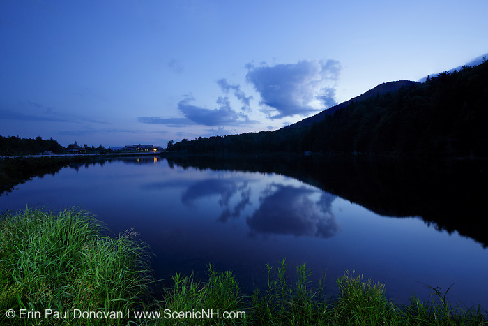 Saco Lake located at the start of Crawford Notch State Park in the White Mountains of New Hampshire USA during morning blue hour. The Appalachian Mountain Club's Highland Center is off in the distance.