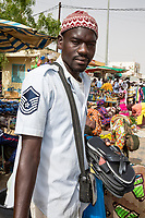 Senegal, Touba.  Young Man Selling Sandals in the Market.