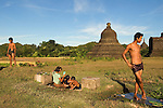 Mrauk U Myanmar (Burma) 2008. After work in the fields, young men wash against a backdrop of Lay Mye Thna Temple, built in 1430