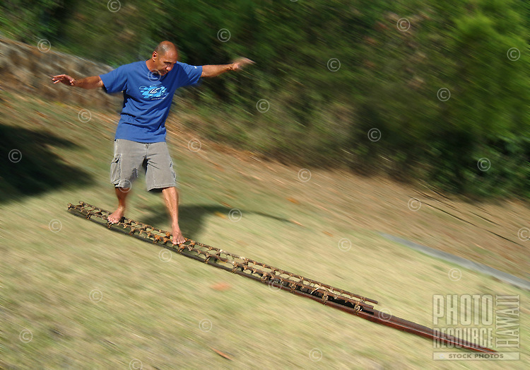 Instructor Tom Pohaku Stone demonstrates the standing position on a holua sled. Holua was a dangerous sport practiced by ancient Hawaiians in honor of the volcano goddess, Madame Pele.