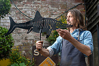 BNPS.co.uk (01202 558833)<br /> Pic: ZacharyCulpin/BNPS<br /> <br /> Pictured: Graham with a prehistoric design<br /> <br /> Something in the wind..<br /> <br /> While Covid caused much of the world to slow down, business has been booming for weathervane maker Graham Smith.<br /> <br /> The former precision engineer has been so busy he has been working seven days a week and has had to close his books to new orders.<br /> <br /> Graham hand-crafts all his weathervanes, creating intricate designs and can even recreate families or significant events.<br /> <br /> With people stuck at home in lockdown and looking at DIY and home improvements, he said he has had his busiest year.