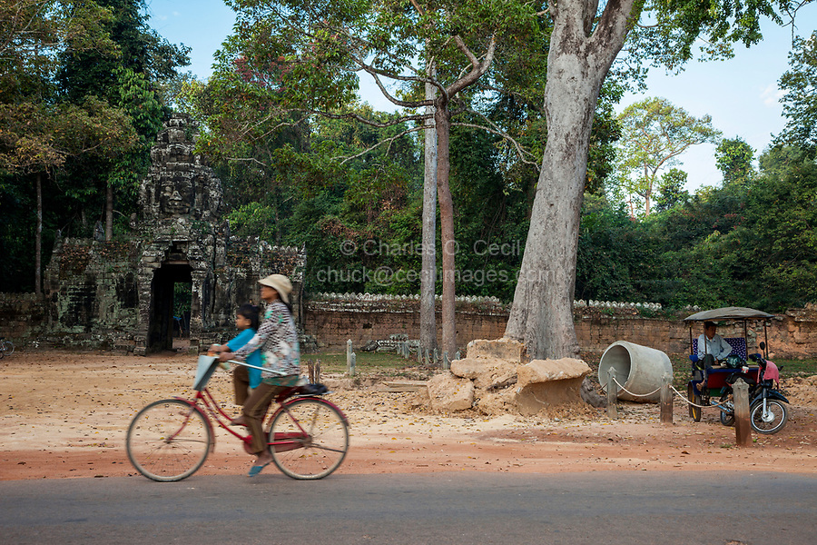 Cambodia.  Woman and Child Riding past Eastern Face-tower Entrance to Banteay Kdei, opposite Srah Srang, Royal Bath.  12th-13th. Century.  A motorcycle taxi waits for a passenger.