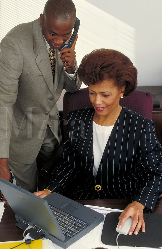 Man and woman conducting business on the telephone, working on laptop. Professionals. Businesswoman. Businessman. African American. Ethnic. Denver Colorado USA.