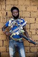 An Anti-Balaka (Anti-Machete) fighter holding a home-made sword and draped with 'Gris Gris' amulets that confer good fortune and protection on the wearers. They are animist in origin but also worn by both Muslims and Christians throughout west and central Africa. In late 2012 after years of instability and conflict, the Seleka, a predominantly Muslim rebel group, fuelled by grievances against the government, overran the country and, In March 2013, ousted President Francois Bozize, who fled the country. The rebel's leader Michel Djotodia was proclaimed president in August 2013. He disbanded the Seleka in September 2013 but law and order collapsed and ex-Seleka fighters roamed the country committing atrocities against the civilian population. In an attempt to defend their lives and property vigilante groups, calling themselves Anti-Balaka (Anti-Machete), formed to confront the ex-Seleka fighters but soon began to take reprisals against the wider Muslim population and the conflict became increasingly sectarian. By December 2013, with international fears of a genocide being voiced, French led peacekeepers deployed to the country began to act on a UN mandate to disarm the fighters and protect the civilian population. However, they have struggled to contain the situation. Much of the Muslim population, in particular, have been forced into ghettos where they are suffering from food shortages and limited access to healthcare. Often, only a few peacekeepers stand between them and a massacre by vengeful Anti-Balaka militants. UN reports describe 'thousands' killed, while over 600,000 people have been internally displaced and a further 200,000 have fled the county.