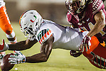 Miami kick returner Mark Walton dives on a fumbled kick return with FSU Javien Elliott in pursuit in the first half of an NCAA college football game against Miami in Tallahassee, Fla., Saturday, Oct. 10, 2015.   The Florida State Seminoles defeated the Miami Hurricanes 29-24.