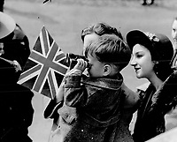 La visite du Roi George VI au Canada en 1939.<br /> <br /> <br /> <br /> <br /> <br /> La visite du Roi George VI au Canada en 1939.<br /> <br /> <br /> <br /> <br /> <br /> This little fellow isn't very tall in his own right; but when he gets up in his mother's arms he towers above bigger folk - notably his sister behind; who stands on tiptoe; trying to get a glimpse of the King and Queen. In fact; she seems to be trying to snatch a look through his binoculars. This was in Montreal.<br /> <br /> [unknown]<br /> Picture, 1939<br /> <br /> PHOTO : Toronto Star Archives - AQP