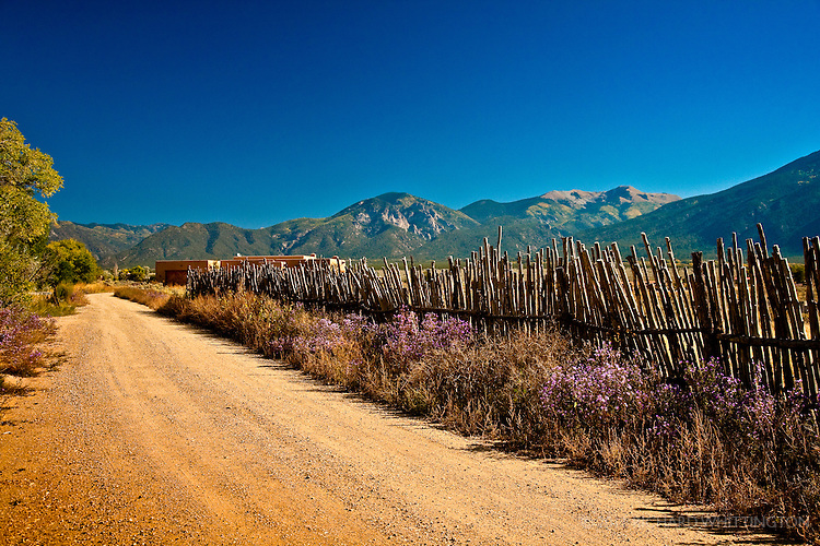 New Mexican landscape near El Prado just North of Taos. Coyote fence lined road below Wheeler Peak, the tallest mountain in New Mexico at 13,141 feet. El Prado, New Mexico north of Taos.