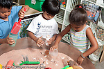 Education Preschool 3-5 year olds sand table two boys and a girl playing separately horizontal