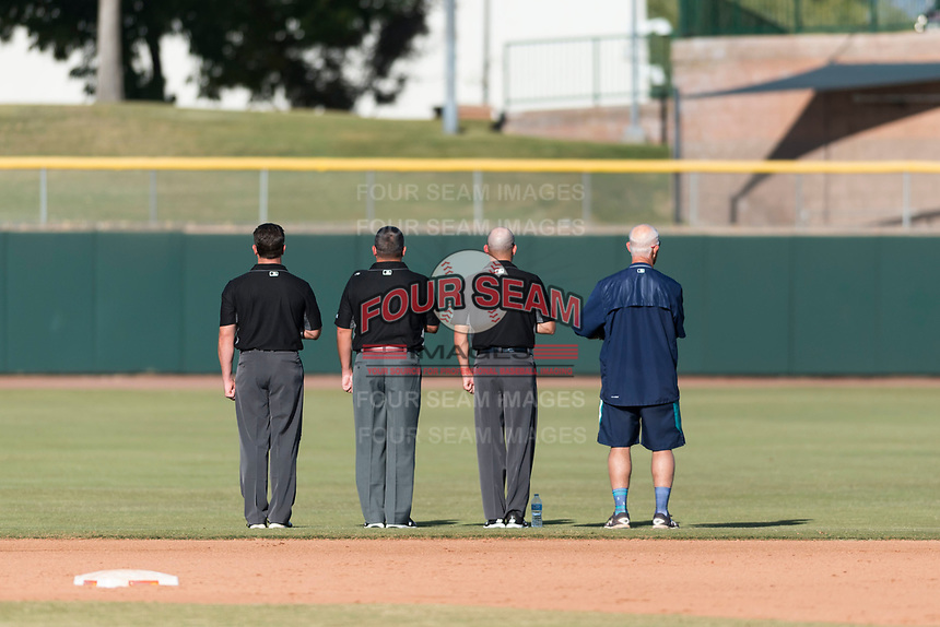 """Field umpires Dan Merkel, Jeremy Riggs, and Dan Wood stand along the outfield grass with bat boy Danny Wood during the singing of """"God Bless America"""" between innings of the Arizona Fall League Championship game against the Peoria Javelinas at Scottsdale Stadium on November 17, 2018 in Scottsdale, Arizona. Peoria defeated Salt River 3-2 in extra innings. (Zachary Lucy/Four Seam Images)"""