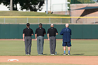 "Field umpires Dan Merkel, Jeremy Riggs, and Dan Wood stand along the outfield grass with bat boy Danny Wood during the singing of ""God Bless America"" between innings of the Arizona Fall League Championship game against the Peoria Javelinas at Scottsdale Stadium on November 17, 2018 in Scottsdale, Arizona. Peoria defeated Salt River 3-2 in extra innings. (Zachary Lucy/Four Seam Images)"