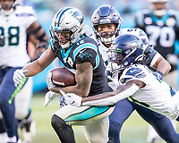 CHARLOTTE, NC - DECEMBER 15: D.J. Moore #12 of the Carolina Panthers attempts to evade the tackle of Tre Flowers #21 of the Seattle Seahawks during a game between Seattle Seahawks and Carolina Panthers at Bank of America Stadium on December 15, 2019 in Charlotte, North Carolina.