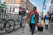 Woman with a walking stick and a shopping trolley, Kilburn, London.