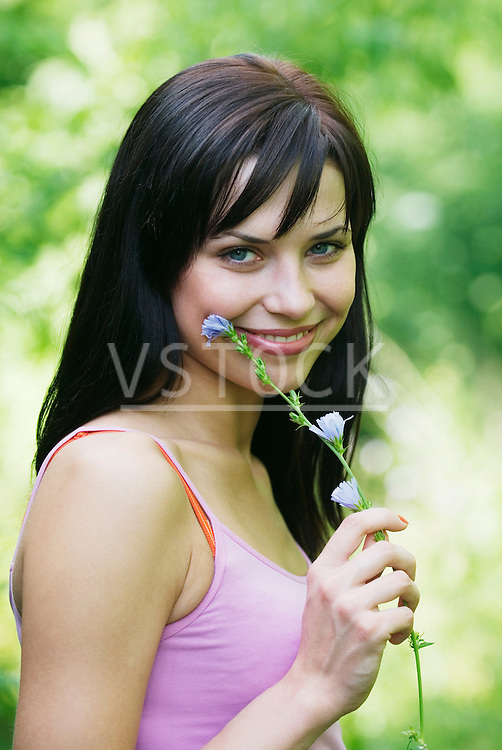 Young woman holding flower, portrait