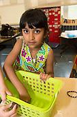 MR / Schenectady, NY. Zoller Elementary School (urban public school). Kindergarten classroom. Portrait of student (girl, 6, bi-racial) cleaning out classroom storage bins. MR: Myk1. ID: AM-gKw. © Ellen B. Senisi.