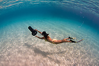 Snorkeler glides over sandy bottom with underwater scooter, Bonaire, Netherland Antilles, Caribbean Sea, Atlantic Ocean, MR