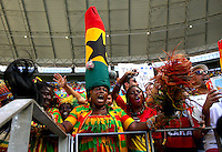 A Ghana fan wearing a large hat cheers her team on