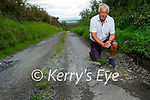 Councillor Robert Beasley standing at road destroyed by potholes in Lahern Ballybunion