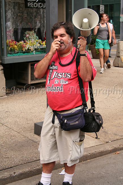 A demonstators marches solo along the streets of Downtown, Pittsburgh preaching about the meaning of Christianity.