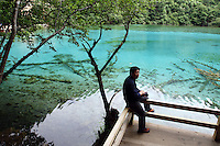 A tourist sitting next to one of the many turquoise lakes in the Jiuzhaigou National Park. Sichuan Province. China.