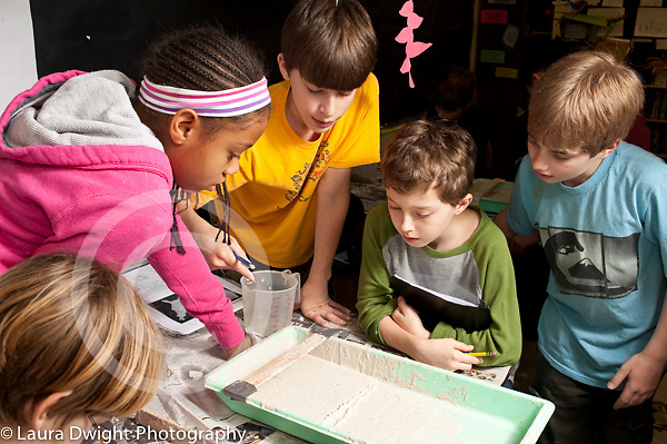 Education elementary Grade 5 science groups working on lab on how flood plains are formed