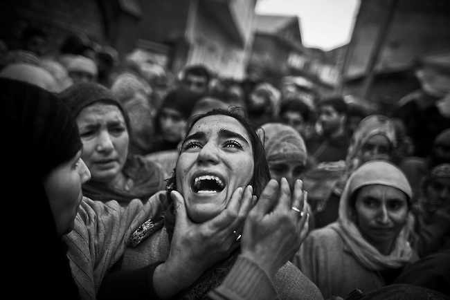 SRINAGAR, KASHMIR, INDIA - FEBRUARY 06: Kashmiri muslims gather to protest the death of teenager Zahid Farooq during his funeral procession on February 06, 2010 on the outskirts of Srinagar, Kashmir, India. Over a thousand Kashmiri's gathered to protest the death of the second teenager in a week, 16 year old student Zahid Farooq. Relatives say Farooq was shot dead by Indian security forces on Friday. (Photo by Daniel Berehulak/Getty Images)