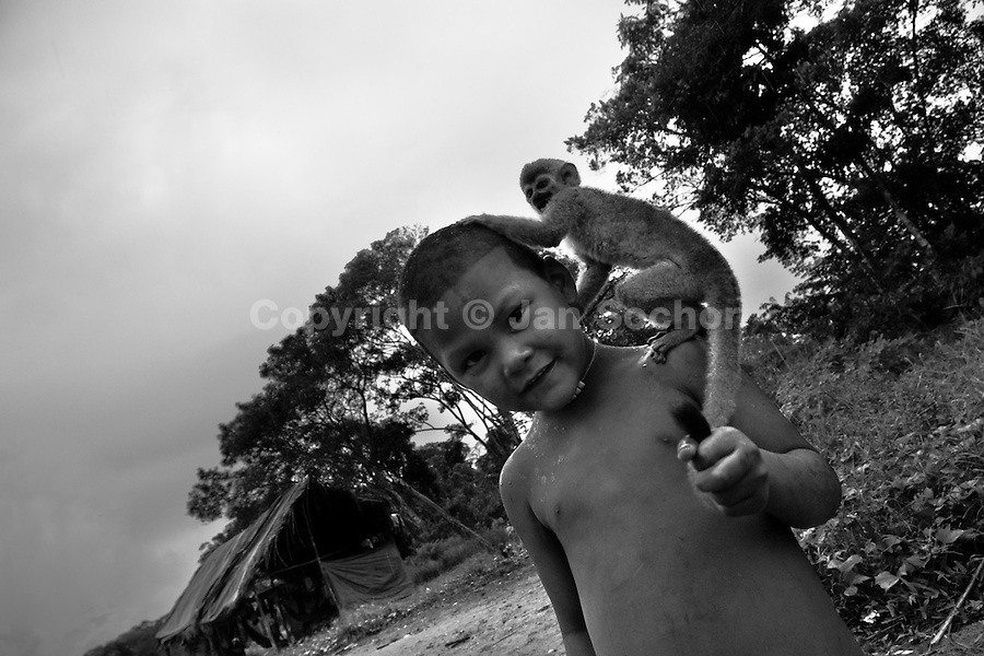 A displaced Indian boy (Nukak Maku) plays with his monkey pet in a refugee settlement close to San Jose del Guaviare, Meta dept., Colombia, 4 September 2009. With nearly fifty years of armed conflict, Colombia has the highest number of civil war refugees in the world. During the last ten years of the civil war more than 3 million people have been forced to abandon their lands and to leave their homes due to the violence. Internally displaced people (IDPs) come from remote rural areas, where most of the clashes between leftist guerrillas FARC-ELN, right-wing paramilitary groups and government forces takes place. Displaced persons flee in a hurry, carrying just personal belongings, and thus they inevitably end up in large slums of the big cities, with no hope for the future.
