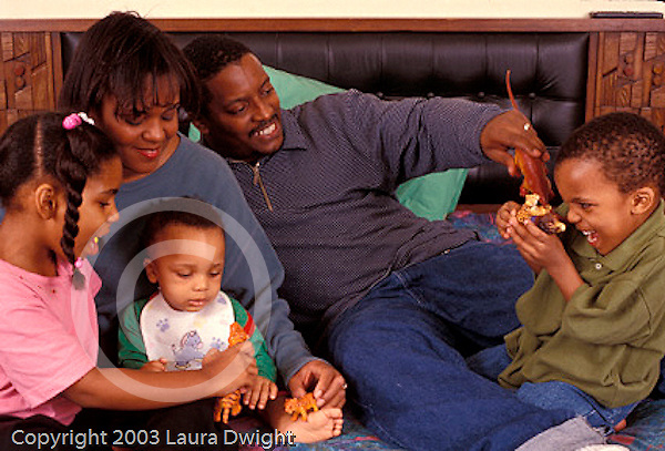 Parents playing with children, daughter age 7 and sons ages 3 and 10 months old.Hispanic-American Dominican and African-American