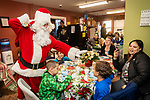 TORRINGTON, CT. 20 December 2019-122019BS09 - Santa greets Tyler Perez, 9, right, as his brother Mason Perez, 7, center, eats his cookies, during a visit by Santa at the FISH of Northwestern Connecticut Homeless Shelter in Torrington on Friday. Bill Shettle Republican-American