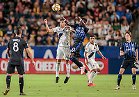 CARSON, CA - SEPTEMBER 21: Joe Corona #14 of the Los Angeles Galaxy and Bacary Sagna #33 of the Montreal Impact battle in the air for a ball during a game between Montreal Impact and Los Angeles Galaxy at Dignity Health Sports Park on September 21, 2019 in Carson, California.