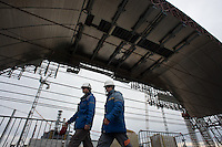 Workers of Chernobyl Nuclear Power Plant. On the background - new gigantic arch and 4th reactor.
