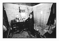 Wang Xu Qing, 77, stands amongst drying peanuts in her tiny single-room home in the clay brick traditional village. Mrs Wang has rarely left the village since she arrived more than 50 years ago. She is a widow of a soldier with no children and worries about how she will feed herself when she is unable to tend her tiny plot of land where she grows subsistence crops of rice and peanuts. She is so poor crushes the peanuts to make cooking oil. She has no income whatsoever....PHOTO BY SINOPIX