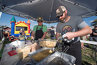 NWA Democrat-Gazette/J.T. WAMPLER Shane Zimmerman, (left) and Levi Rush prepare alligator meat for frying Sunday Oct.2, 2016 at the Downtown Rogers Farmers Market. Two alligators and two wild hogs were  harvested by Hannah Ciceroni in south Texas last week.  Local chefs cooked the fresh gators and hogs, each putting their own touches on the wild meat as a fundraiser for Main Street Rogers.