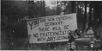 BNPS.co.uk (01202) 558833. <br /> Pic: Bosleys/BNPS<br /> <br /> Pictured: SAS troops pass a sign on the German boarder. <br /> <br /> Never before seen photos taken by a fishmonger turned SAS hero behind enemy lines in World War Two have come to light 76 years on.<br /> <br /> Sergeant Samuel Rushworth, of the 2nd Special Air Service, was dropped into occupied France two days before D-Day in June 1944.<br /> <br /> They were tasked with disrupting German reinforcements dispatched to Normandy following the Allied landings.