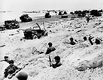 Sitting in the cover of their foxholes, American soldiers of the Allied Expeditionary Force secure a beachhead during  initial landing operations at Normandy, France, June 6, 1944. In the background amphibious tanks and other equipment crowd the beach, while landing craft bring more troops and material ashore. (AP Photo/Weston Haynes)