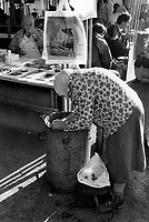 Russia. Krasnodar Krai Region. Krasnodar. City center. A poor elderly woman collects food in a trash can in a public market. A stall sells plastic bags with a dog and a beautiful young woman in swimsuit. Krasnodar (also known as Kuban) is the largest city and the administrative centre of Krasnodar Krai in Southern Russia. 20.09.1993 © 1993 Didier Ruef