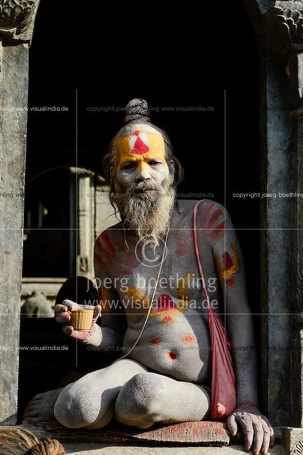 NEPAL Kathmandu, Pashupatinath Hindu Temple, ash saearded sadhu drinks Chai, tea / Asche beschmierter Sadhu trinkt Tee