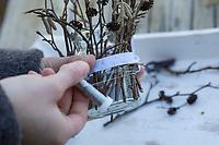 Windlicht, Windlichter, Waldlicht, Waldlichter, Wind-Licht, Wind-Lichter, ein Glas wird von außen mit Stöckchen, Ästchen, Ästen dekoriert. Im Glas steht und brennt windgeschützt eine Kerze, Bastelei mit Naturmaterialien. Schritt 2: dekorativer Draht wird unterhalb des Gummibandes so gespannt, dass die Äste festhalten. Später kann das Gummiband entfernt werden