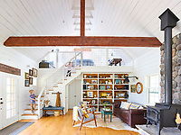 The open-plan living space has a high, vaulted ceiling and exposed beams. the wood panelling is painted in White Opulence by Benjamin Moore. The energy efficient wood-burning stove provides<br /> heat without any smoke emissions and the hearth is man-made rock, cast from stones from the Sierra Mountains.