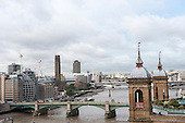 Southwark bridge, London, England. High view of River Thames with modern buildings and old towers, green and yellow Southwark Brdge