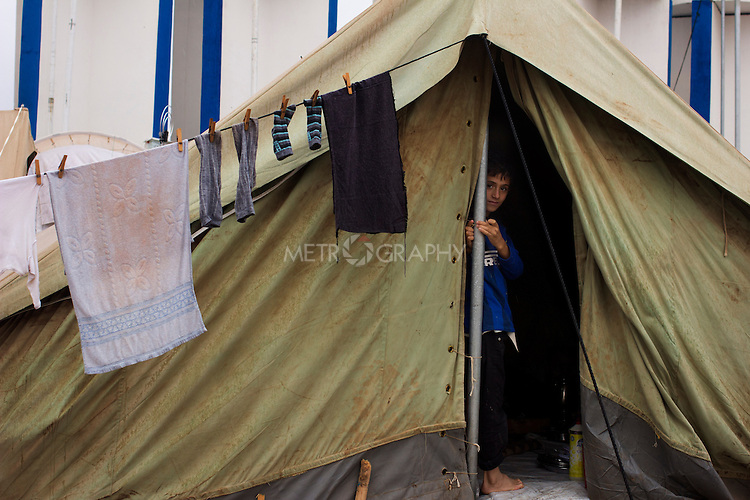 DOMIZ, IRAQ: A young Syrian refugee looks out his tent in the Domiz refugee camp in the Kurdish region of northern Iraq...The semi-autonomous region of Iraqi Kurdistan has accepted around 60,000 refugees from war-torn Syria. Around 20,000 refugees live in the Domiz camp which sits 60 km from the Iraq-Syria border...Photo by Younes Mohammad/Metrography