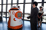 """August 01 2012, Tokyo, Japan - The president of Tokyo Tower, Shin Maeda hands over the employee ID to the new robot guide. Tokyo Tower implemented the new robot guide which name is """"Tawabo"""", the first indoor robot guide in Japan. It can speak Japanese, English, Chinese and Korean, it weights 200kg and it is 160cm tall."""