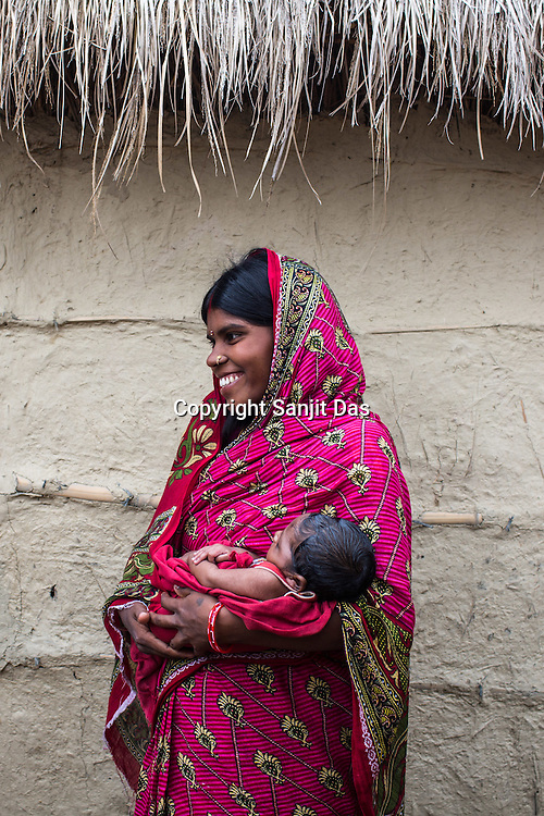 25 year old Sri Kanthi Devi seen in a positive mood as she holds her 3 months old son, Chandan Kumar in her house in Ramgarwa village in Raxaul district in Bihar, India.