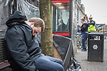 © Joel Goodman - 07973 332324 . 06/04/2017 . Manchester , UK . A paramedic tends to a man , believed to have consumed spice , in Piccadilly Gardens , as another man consumes a rolled cigarette believed to contain spice , in an adjacent telephone box and a third man lies slumped on a bench . An epidemic of abuse of the drug spice by some of Manchester's homeless population , in plain sight , is causing users to experience psychosis and a zombie-like state and is daily being witnessed in the Piccadilly Gardens area of Manchester , drawing large resource from paramedic services in the city centre . Photo credit : Joel Goodman
